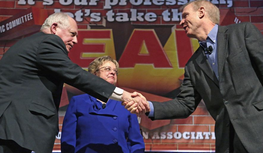 FILE - In this April 11, 2014 file photo, Illinois Gov. Pat Quinn, left, and his Republican rival, businessman Bruce Rauner, shake hands after they appeared together at the annual meeting of the Illinois Education Association in Chicago. Illinois has seen a roughly 30 percent increase in the number of TV ads and the money spent to air them this election cycle compared to four years ago, according to an analysis by the non-partisan Center for Public Integrity. That jump has been fueled by the neck-and-neck race between Rauner and Quinn. (AP Photo/M. Spencer Green, File)