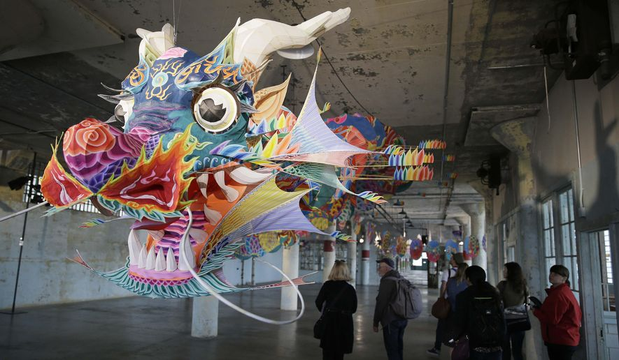 People walk past a dragon kite that is part of the installation With Wind during a preview of the art exhibit @Large: Ai Weiwei on Alcatraz Island Wednesday, Sept. 24, 2014, in San Francisco. Revealing unexpected perspectives on Alcatraz and its layered legacy, the exhibit by the Beijing-based artist prompts visitors to consider the implications of incarceration and the possibilities of art as an act of conscience. The exhibit, which opens Friday and runs through April, features 175 portraits of prisoners of conscience and political exiles around the world, from Nelson Mandela and the Tibetan pop singer Lolo to the American whistle-blower Edward Snowden and composed of 1.2 million Lego pieces. (AP Photo/Eric Risberg)