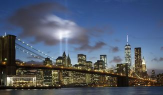 FILE - In this Sept. 10, 2014 file photo, the Tribute in Light rises behind the Brooklyn Bridge and buildings adjacent to the World Trade Center complex in New York. The tribute, an art installation of 88 searchlights aiming skyward in two columns, is a remembrance of the Sept. 11, 2001, attacks.  The New York City licensing test for sightseeing guides includes questions about the bridge and the trade center.  (AP Photo/Mark Lennihan, File)