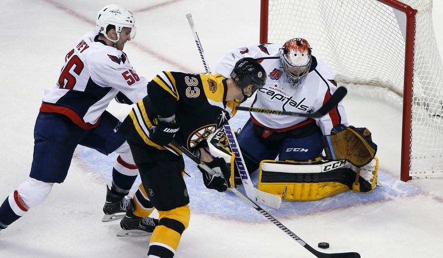 Boston Bruins defenseman Zdeno Chara scores a goal against Washington Capitals goalie Pheonix Copley as Patrick Wey (56) tries to defend during the third period of an NHL preseason hockey game in Boston, Wednesday, Sept, 24, 2014. The Bruins won 2-0. (AP Photo/Elise Amendola)