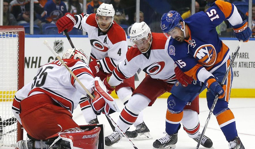 Carolina Hurricanes goalie Drew MacIntyre (35) stops a shot by New York Islanders right wing Cal Clutterbuck (15) as Hurricanes defenseman Andrej Sekera (4) and forward Brad Malone (24) help out during the second period of a preseason NHL hockey game Wednesday, Sept. 24, 2014, in Uniondale, N.Y.  (AP Photo/Paul Bereswill)