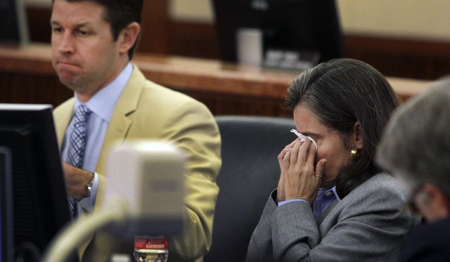 Dr. Ana Maria Gonzalez-Angulo, right, wipes her eyes after her defense attorney Derek Hollingsworth, left, finished his closing argument in her trial, Wednesday, Sept. 24, 2014, in Houston. Gonzalez-Angulo, a breast cancer doctor, is accused of spiking researcher George Blumenschein's coffee in 2013 with a chemical found in antifreeze. Blumenschein survived. (AP Photo/Houston Chronicle, Melissa Phillip)