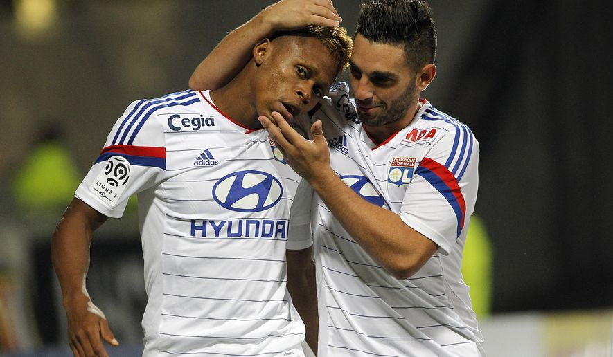 Lyon's Clinton Mua Njie, left, celebrates with Jordan Ferri, right, after he scored a goal against Lorient during their French League One soccer match in Lyon, central France, Wednesday, Sept. 24, 2014. (AP Photo/Laurent Cipriani)