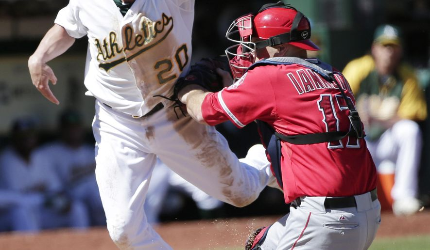 Oakland Athletics' Josh Donaldson, left, is tagged out at the plate by Los Angeles Angels catcher Chris Iannetta as he tried to score on a sacrifice fly from Derek Norris during the fourth inning of a baseball game on Wednesday, Sept. 24, 2014, in Oakland, Calif. (AP Photo/Marcio Jose Sanchez)