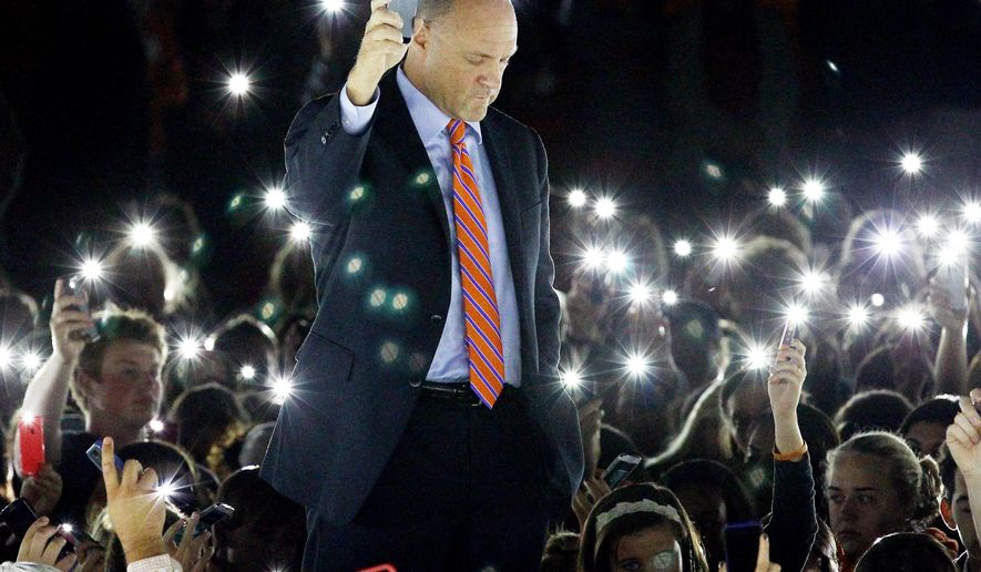 In this Tuesday, Sept. 23, 2014 photo, Jim Clements, president of Clemson University, leads a moment of silence during a vigil for Tucker Hipps as people use their cell phones to illuminate Bowman Field in Clemson, S.C. One day after Hipps fatally fell from a bridge after a run with his fraternity brothers, Clemson University suspended activities for all of its fraternities, citing reports of alcohol abuse and sexual misconduct but stopping short of tying the ban to the death. (AP Photo/Anderson Independent Mail, Nathan Gray)