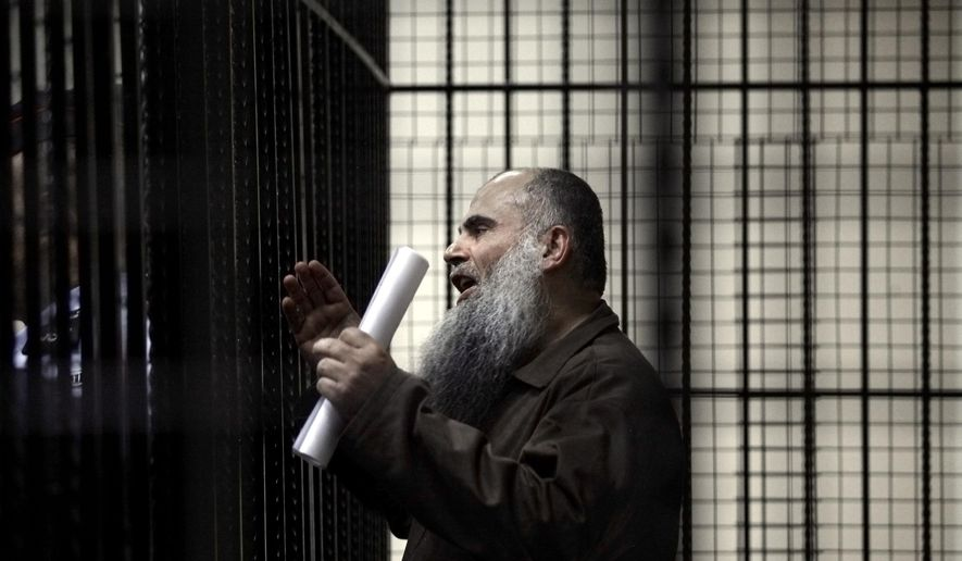 In this Sunday, Sept. 7, 2014, file photo, radical al Qaeda-linked preacher Abu Qatada speaks to the press prior to his verdict at the Jordanian military court in Amman, Jordan.  On Wednesday, Sept. 24, 2014, a Jordanian military court acquitted Abu Qatada on terrorism charges, for his role in plotting attacks against Americans and Israelis, ruling there was insufficient evidence. The decision was handed down in the case presided over by civilian judges in the Jordanian capital, Amman. (AP Photo/Mohammad Hannon, File)