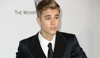 In this May 22, 2014, file photo, Justin Bieber arrives at the amfAR Cinema Against AIDS benefit at the Hotel du Cap-Eden-Roc, during the 67th international film festival, in Cap d'Antibes, southern France. (Photo by Joel Ryan/Invision/AP, file)