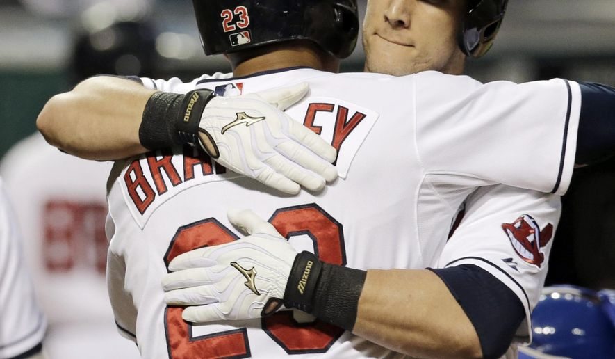 Cleveland Indians' Yan Gomes, right, embraces Michael Brantley after Gomes hit a three-run home run off Kansas City Royals starting pitcher Jason Vargas in the first inning of a baseball game, Wednesday, Sept. 24, 2014, in Cleveland. Brantley and Carlos Santana scored on the play. (AP Photo/Tony Dejak)