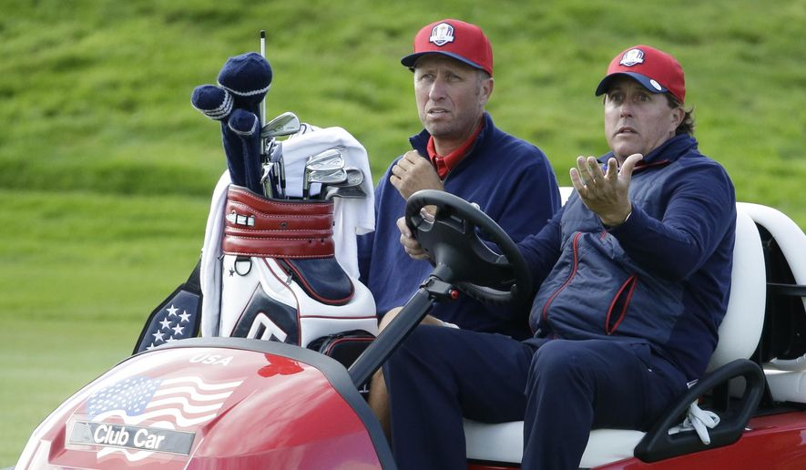 Phil Mickelson of the U.S. drives off the 4th hole with his caddie Jim Mackay during a practice round ahead of the Ryder Cup golf tournament at Gleneagles, Scotland, Wednesday, Sept. 24, 2014. (AP Photo/Matt Dunham)