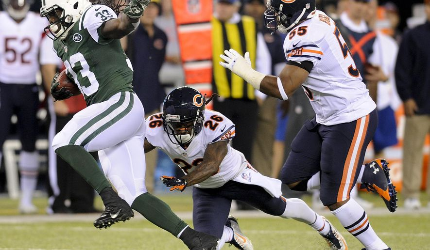 New York Jets running back Chris Ivory (33) tries to avoid a tackle by Chicago Bears cornerback Tim Jennings (26) and outside linebacker Lance Briggs (55) in the first quarter of an NFL football game, Monday, Sept. 22, 2014, in East Rutherford, N.J. (AP Photo/Bill Kostroun)