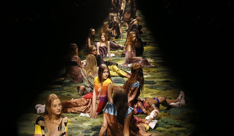 Models sit on the catwalk during Dries van Noten's Spring/Summer 2015 ready-to-wear fashion collection presented in Paris, France, Wednesday, Sept. 24, 2014. (AP Photo/Jacques Brinon)