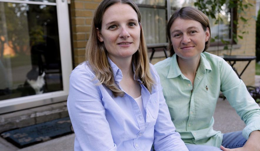 Barbara Webb, 33, of Madison Heights, left, poses for a portrait on Sept. 2, 2014, with her wife Kristen Lasecki, 33, in Detroit Webb is now a former chemistry teacher at a Catholic, all-girls high school in Bloomfield Hills. The Catholic nuns who operate Marian High School plan to re-examine policies regarding the decision to fire Webbafter she became pregnant. (AP Photo/Detroit Free Press, Mandi Wright)  DETROIT NEWS OUT;  NO SALES