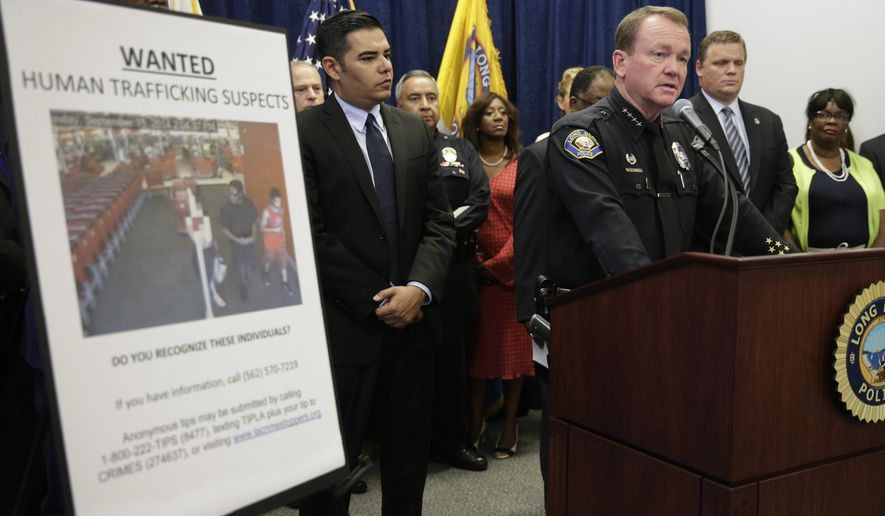 Long Beach Police Chief Jim McDonnell, right, joined by mayor Robert Garcia, center, speaks during a news conference held at Long Beach Police Department headquarters Wednesday, Sept. 24, 2014, in Long Beach, Calif. Authorities said a crackdown on sex trafficking in Southern California has led to 91 arrests and the rescue of nearly two dozen children who had been forced into prostitution. (AP Photo/Jae C. Hong)