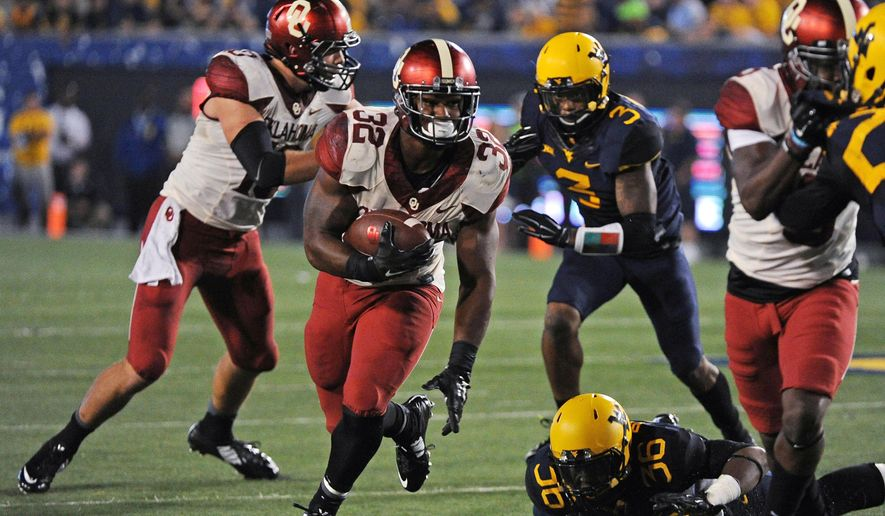 Oklahoma's Samaje Perine (32) runs for a first down during the fourth quarter of an NCAA college football game against West Virginia in Morgantown, W.Va., on Saturday, Sept. 20, 2014. (AP Photo/Tyler Evert)