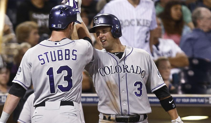 Colorado Rockies' Drew Stubbs is congratulated by Michael Cuddyer after his solo home run against the San Diego Padres in the eighth inning of a baseball game Tuesday, Sept. 23, 2014, in San Diego.  (AP Photo/Lenny Ignelzi)