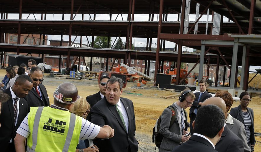 Gov. Chris Christie, center, greets a worker at the construction of a huge new KIPP Cooper Norcross Academy school Wednesday, Sept. 24, 2014, in Camden, N.J. Christie has made frequent stops in the high-crime city, stressing his efforts working with local Democratic lawmakers, including Mayor Dana Redd. The governor said he's been in Camden more than any other city in New Jersey and has watched the change firsthand. (AP Photo/Mel Evans)