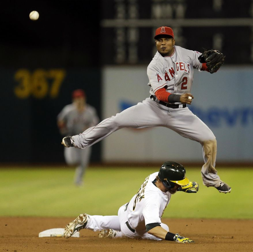Los Angeles Angels shortstop Erick Aybar hops over Oakland Athletics' Josh Reddick after completing a double play in the seventh inning of a baseball game Tuesday, Sept. 23, 2014, in Oakland, Calif. Oakland's Geovany Soto was out at first base. (AP Photo/Ben Margot)