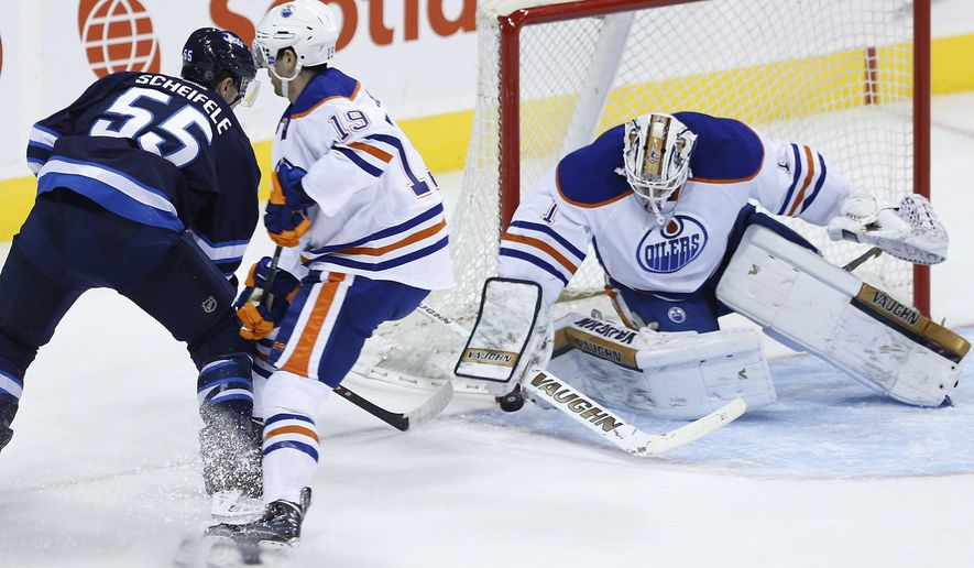Edmonton Oilers' Justin Schultz (19) and goaltender Laurent Brossoit (1) shut down Winnipeg Jets' Mark Scheifele (55) as he attempts a wraparound during the first period of an NHL preseason hockey game Wednesday, Sept. 24, 2014, in Winnipeg, Manitoba. (AP Photo/The Canadian Press, John Woods)