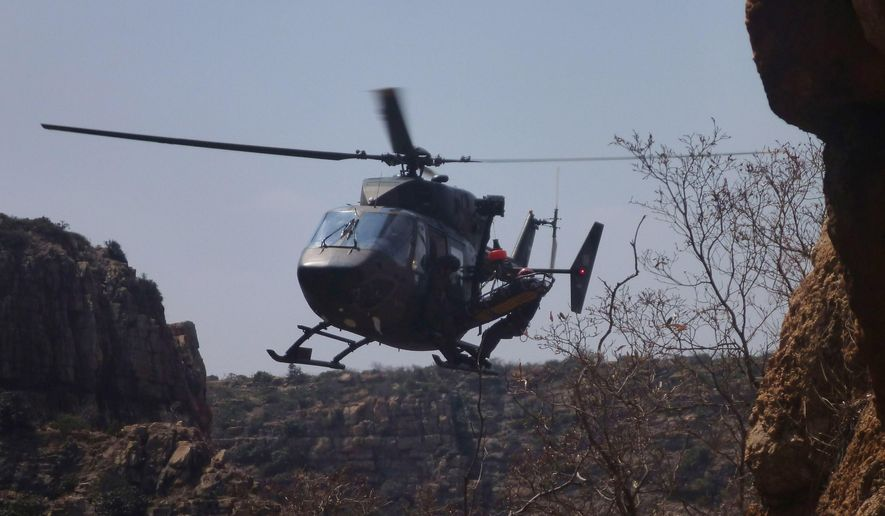 In this  handout photo supplied by the Mountain Club of SA Search and Rescue and taken Sunday Sept. 21, 2014 a helicopter is loaded with a stretcher carrying  Tsenolo Shadrack Rasello from The Kloof, a tourist destination near Johannesburg in Rustenburg South Africa. South African rescue workers recently performed surgery on the side of a cliff, amputating the leg of  Rasello, whose foot was jammed between rocks in a drama reminiscent of the ordeal of Aron Ralston, the American climber who cut off his own arm to escape from a remote Utah canyon.  Rasello used his cellular telephone, setting off a tense and complex rescue operation that included several helicopters and more than 100 people. (AP Photo/Mountain Club of SA Search and Rescue )   MANDATORY CREDIT