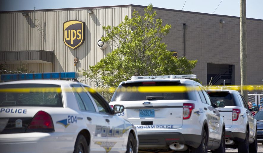 A UPS warehouse has police cars and tape surrounding it on Tuesday, Sept. 23, 2014, in Birmingham, Ala. A UPS employee opened fire Tuesday morning inside one of the company's warehouses in Alabama, killing two people before taking his own life, police said.(AP Photo/Brynn Anderson)