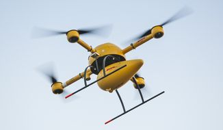 """This Sept. 2014 photo provided by Deutsche Post/DHL shows a flying DHL drone in Germany. Deutsche Post/DHL says Wednesday, Sept. 24, 2014, it is starting Germany's first ever drone package delivery service, a test program transporting medication to a pharmacy on a difficult-to-access North Sea island. The company said the quad-rotor """"DHL Paketkopter 2.0"""" will begin daily flights Friday to bring a maximum payload of 1.2 kilograms of medicine to the island of Juist. The island, with a population of about 1,500, is usually served by one ferry per day and an occasional small-aircraft flight, depending upon the weather. (AP Photo/Nikolai Wolff Fotoetage)"""