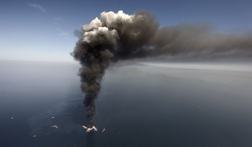 FILE -  In this Wednesday, April 21, 2010 file photo, oil can be seen in the Gulf of Mexico, more than 50 miles southeast of Venice on Louisiana's tip, as a large plume of smoke rises from fires on BP's Deepwater Horizon offshore oil rig. The oil giant argued Wednesday, Sept. 24, 2014, before a federal judge that a flawed funding formula in a settlement the company agreed to after the oil spill is giving money to businesses for questionable claims, and they should be forced to give it back. (AP Photo/Gerald Herbert, File)