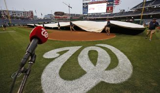 Members of the Washington Nationals grounds crew covers the field before a baseball between the Nationals and the New York Mets at Nationals Park, Wednesday, Sept. 24, 2014, in Washington. (AP Photo/Alex Brandon)