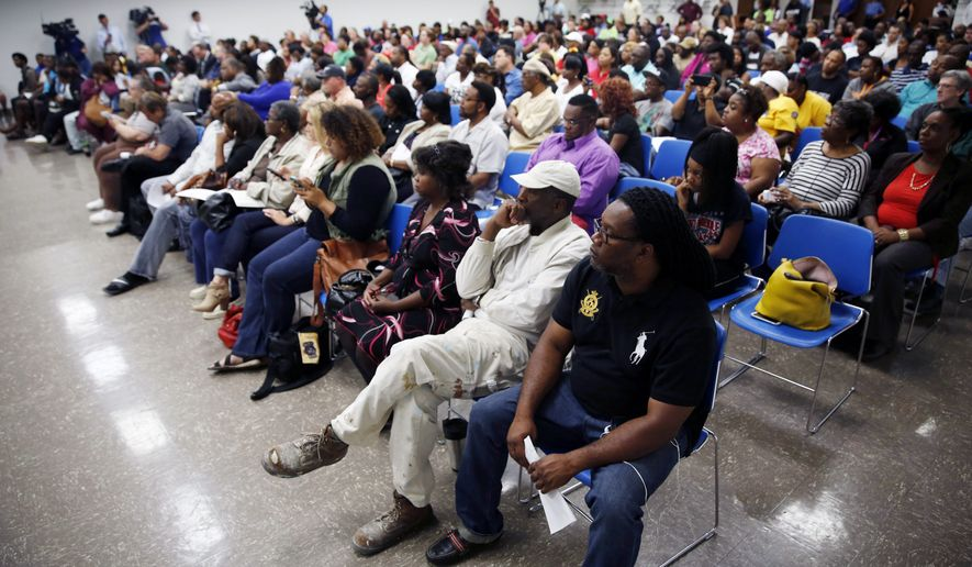 Several hundred people pack a room on the St. Louis Community College Florissant Valley campus during a meeting held by the Department of Justice to talk about the agency's investigation of the Ferguson police department Wednesday, Sept. 24, 2014, in Ferguson, Mo. Members of the Department of Justice also spoke with people individually about their interactions with Ferguson police and other law enforcement agencies in St. Louis County. (AP Photo/Jeff Roberson)