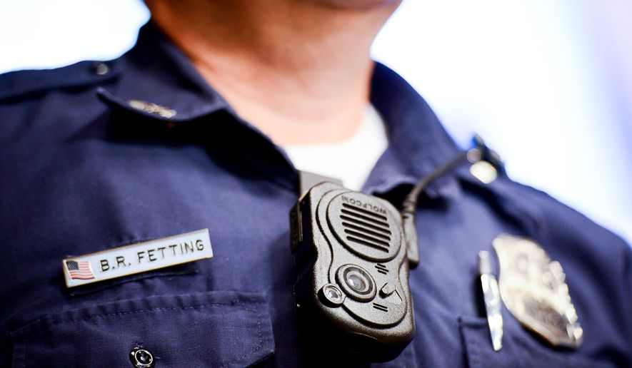 Officer Benjamin Fetting models a wolfcom radio that has a camera built into it as Washington, D.C. MPD Chief Cathy Lanier announces that the police department is testing five different kinds of body-worn cameras during a pilot program, during a press conference at the Wilson Building, Washington, D.C., Wednesday, Sept. 24, 2014. (Andrew Harnik/The Washington Times) ** FILE **