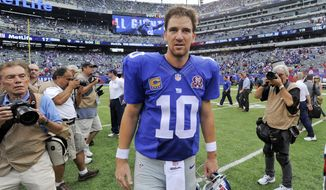 New York Giants quarterback Eli Manning (10) walks off the field after the Giants beat the Houston Texans 30-17 in an NFL football game, Sunday, Sept. 21, 2014, in East Rutherford, N.J. (AP Photo/Bill Kostroun)
