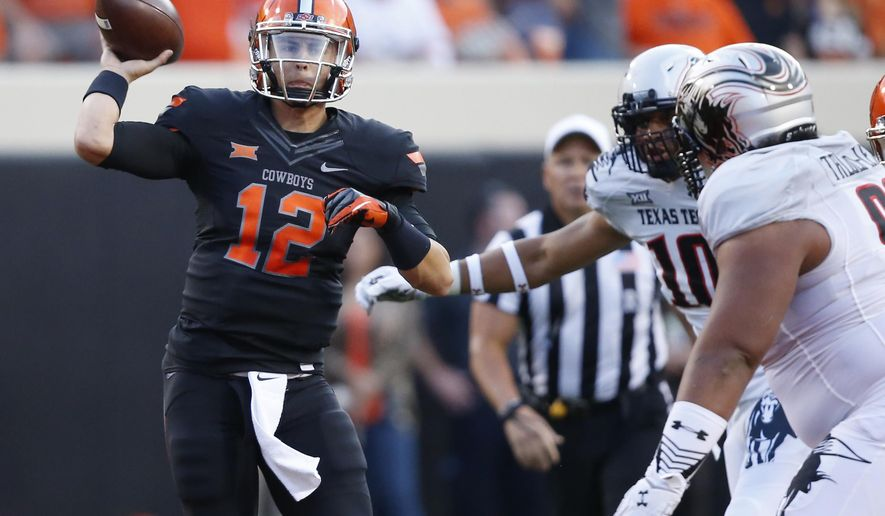 Oklahoma State quarterback Daxx Garman (12) passes under pressure from Texas Tech defenders in the first quarter of an NCAA college football game in Stillwater, Okla., Thursday, Sept. 25, 2014. (AP Photo/Sue Ogrocki)