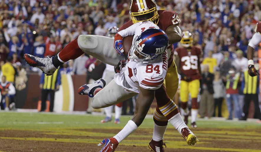 New York Giants tight end Larry Donnell (84) heads to the turf in the end zone after pulling in a touchdown pass under pressure from Washington Redskins inside linebacker Perry Riley (56) during the first half of an NFL football game in Landover, Md., Thursday, Sept. 25, 2014. (AP Photo/Patrick Semansky)