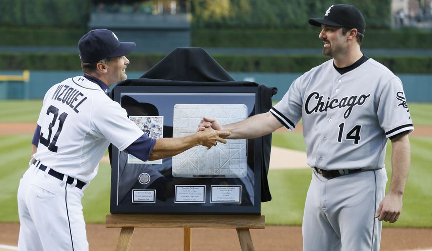 Chicago White Sox designated hitter Paul Konerko (14)  shakes hands with Detroit Tigers first base coach Omar Vizquel (31) while being honored before a baseball game in Detroit Tuesday, Sept. 23, 2014. Konerko will be retiring after the season. (AP Photo/Paul Sancya)