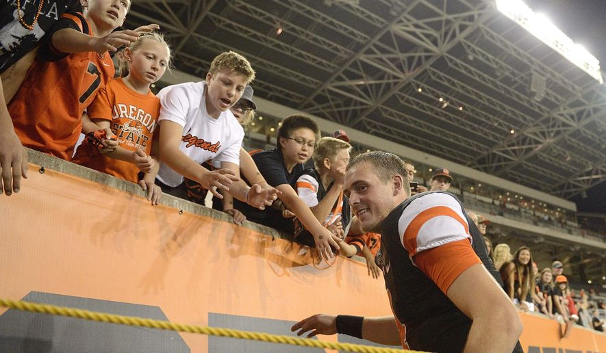 Oregon State quarterback Sean Mannion (4) visits with fans after a game against San Diego State in an NCAA college football game in Corvallis, Ore., Saturday, Sept. 20, 2014. (AP Photo/Troy Wayrynen)