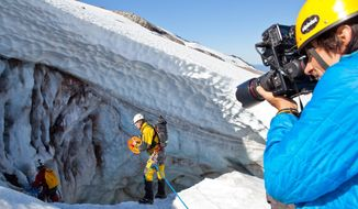 "In this 2013 photo provided by Oregon Field Guide, photographer Andy Maser, right, photographs caver Eddy Cartaya, center, near a glacier cave in the Mount Hood Wilderness area in Oregon for an episode of ""Oregon Field Guide"" for Oregon Public Broadcasting. The U.S. Forest Service said Thursday, Sept. 25, 2014, that it is extending the period for the public to weigh in on a proposal that would make permanent new rules and permit fees for commercial video and still photography in federally designated wilderness areas. (AP Photo/Courtesy Oregon Public Broadcasting, Katie Campbell)"