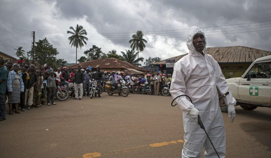 """In this photo taken on Wednesday, Sept. 24, 2014, a healthcare worker sprays disinfectant in the area they found a man suspected of suffering from the Ebola virus in Kenema, Sierra Leone, Thursday, Sept. 25, 2014.  Sierra Leone restricted travel Thursday, Sept. 25, 2014 in three more """"hotspots"""" of Ebola where more than 1 million people live, meaning about a third of the country's population is now under quarantine. Sierra Leone is one of the hardest hit countries in the Ebola outbreak sweeping West Africa that is believed to have killed more than 2,900 people, according to World Health Organization tolls published Thursday. (AP Photo/ Tanya Bindra)"""