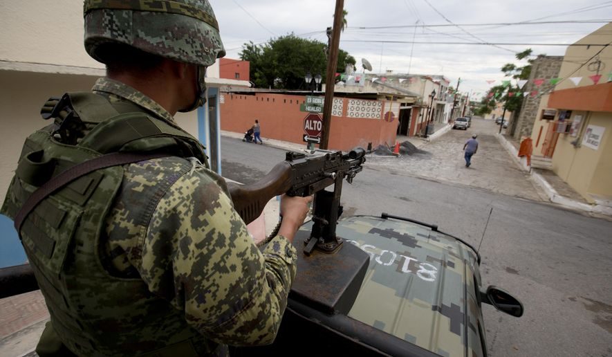 A soldier patrols from the top of a moving vehicle as residents walk in the street in Ciudad Mier, Tamaulipas state, Mexico, Sept. 5, 2014. (Associated Press) ** FILE **