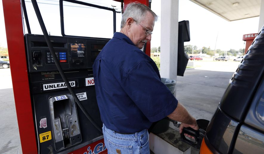 "In this Wednesday, Sept. 24, 2014 photo, Foster Gilley, of Chatom, Ala., fills his SUV's tank with $2.92-per-gallon regular gas at Mac's Gas in Richland, Miss. The typical autumn decline in gasoline prices is getting a big push lower by falling global oil prices. By the end of the year, up to 30 states could have an average gasoline price of under $3 a gallon. Gilley and his wife were visiting his brother in Vicksburg and were ""enjoying the lower prices,"" he said. (AP Photo/Rogelio V. Solis)"