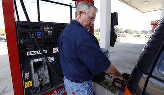"""In this Wednesday, Sept. 24, 2014 photo, Foster Gilley, of Chatom, Ala., fills his SUV's tank with $2.92-per-gallon regular gas at Mac's Gas in Richland, Miss. The typical autumn decline in gasoline prices is getting a big push lower by falling global oil prices. By the end of the year, up to 30 states could have an average gasoline price of under $3 a gallon. Gilley and his wife were visiting his brother in Vicksburg and were """"enjoying the lower prices,"""" he said. (AP Photo/Rogelio V. Solis)"""