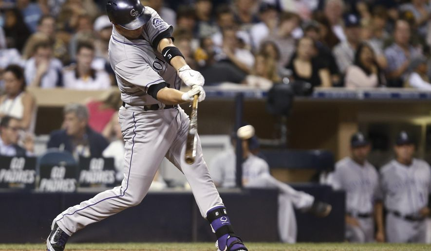 Colorado Rockies' Michael Cuddyer connects for an RBI single against the San Diego Padres in the sixth inning of a baseball game Wednesday, Sept. 24, 2014, in San Diego. (AP Photo/Lenny Ignelzi)
