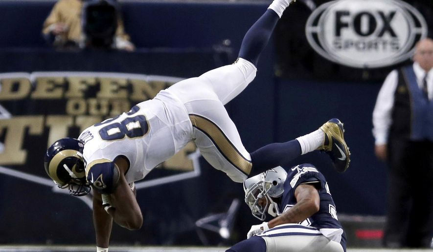 St. Louis Rams tight end Jared Cook, top, is upended by Dallas Cowboys cornerback Orlando Scandrick after catching a pass for an 8-yard gain during the fourth quarter of an NFL football game Sunday, Sept. 21, 2014, in St. Louis. The Cowboys won 34-31. (AP Photo/Jeff Roberson)