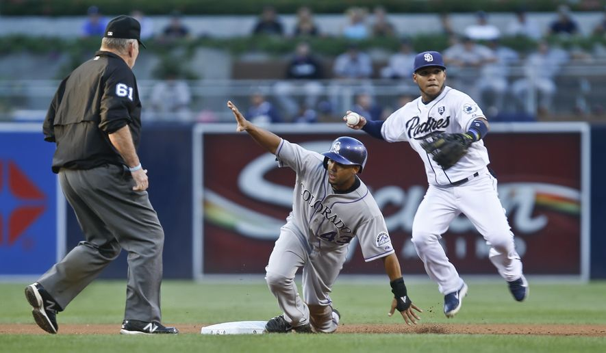 Colorado Rockies' Rafael Ynoa gives umpire Bob Davidson the safe sign as San Diego Padres shortstop Alexi Amarista prepares to relay to first to complete a double play in the first inning of a baseball game Wednesday, Sept. 24, 2014, in San Diego. Davidson ignored Ynoa's call. (AP Photo/Lenny Ignelzi)