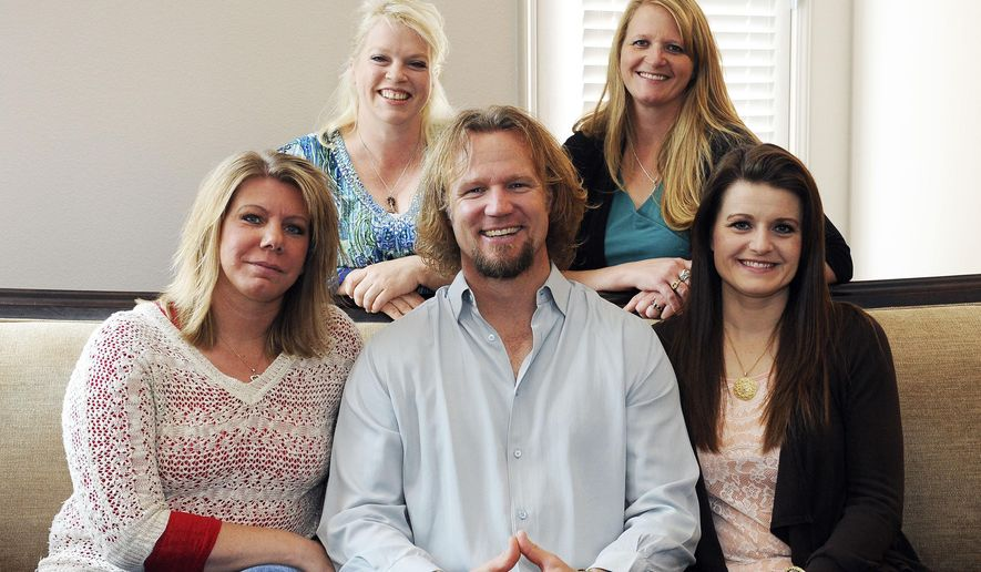 """In this July 10, 2013, file photo, Kody Brown poses with his wives — one is legally his wife and the other are """"sister wives"""" — at one of their homes in Las Vegas. Utah's attorney general has filed notice that he will appeal a ruling striking down parts of the state's anti-polygamy law in a lawsuit brought by the family on the TLC reality TV show, """"Sister Wives."""" Attorney General Sean Reyes filed the notice Wednesday, about a month after a federal judge issued a final ruling in the case. (AP Photo/Las Vegas Review-Journal, Jerry Henkel/File)"""