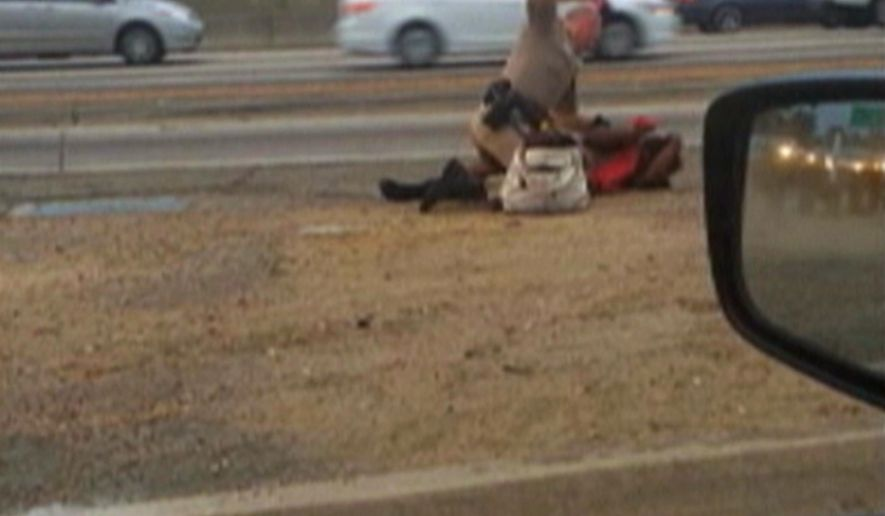 FILE - In this July 1, 2014 file image made from video provided by motorist David Diaz, a California Highway Patrol officer straddles a woman while punching her on the shoulder of a Los Angeles freeway. A woman punched repeatedly by a California Highway Patrol officer in an incident caught on video will receive $1.5 million under a newly reached settlement, and the officer has agreed to resign. CHP Commissioner Joe Farrow confirmed the settlement in an emailed statement Wednesday night  Sept. 24, 2014 and an attorney for Marlene Pinnock confirmed the terms for The Associated Press.  (AP Photo/David Diaz, File)