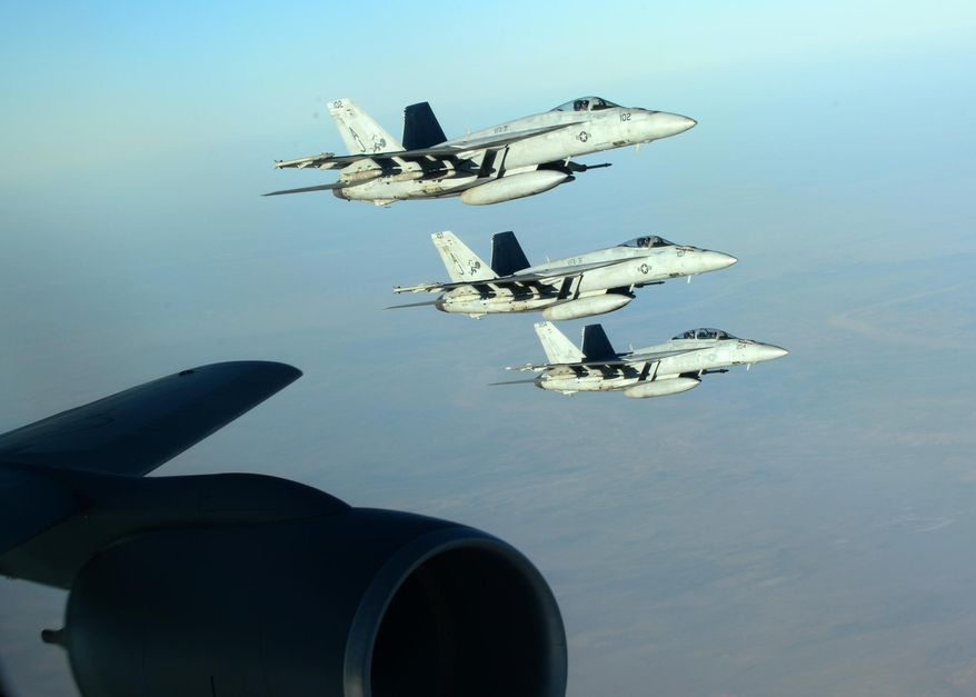 In this Tuesday, Sept. 23, 2014 photo released by the U.S. Air Force, a formation of U.S. Navy F-18E Super Hornets leaves after receiving fuel from a KC-135 Stratotanker over northern Iraq as part of U.S. led coalition airstrikes on the Islamic State group and other targets in Syria. U.S.-led airstrikes targeted Syrian oil installations held by the militant Islamic State group overnight and early Thursday, Sept. 25, 2014, killing nearly 20 people as the militants released dozens of detainees in their de facto capital, fearing further raids, activists said. (AP Photo/U.S. Air Force, Staff Sgt. Shawn Nickel)