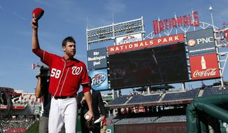 Washington Nationals pitcher Doug Fister, right, acknowledges the fans as he leaves the field after the first baseball game of a doubleheader against the Miami Marlins at Nationals Park, Friday, Sept. 26, 2014, in Washington. The NL East champions locked up home-field advantage until the World Series by beating the Marlins 4-0 on Fister's three-hitter. (AP Photo/Alex Brandon)