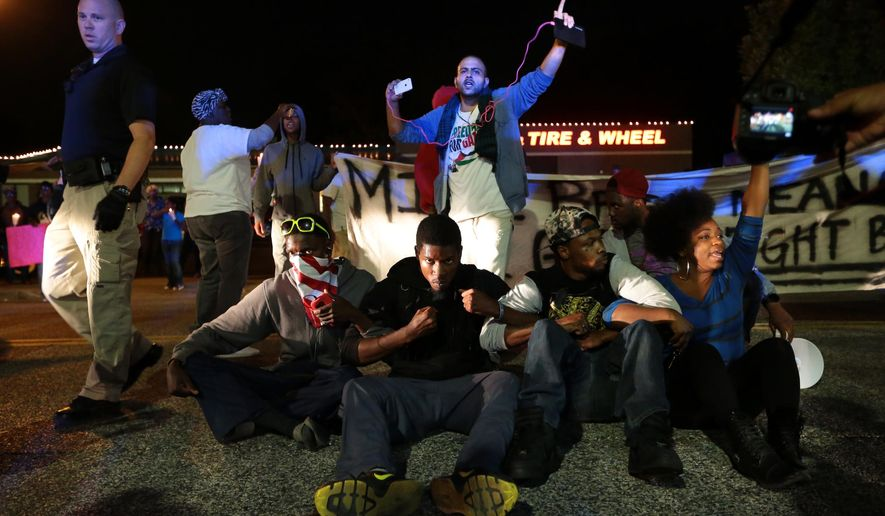 Protesters lock arms, blocking S. Florissant Road in front of the Ferguson Police Department, calling for the resignation of Police Chief Tom Jackson on Thursday, Sept. 25, 2014. (AP Photo/St. Louis Post-Dispatch, Robert Cohen) ** FILE **