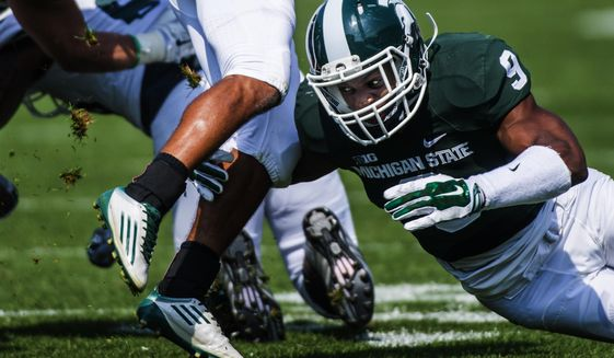 Michigan State freshman defensive back Montae Nicholson tackles Eastern Michigan senior wide receiver Tyler Allen as grass flies up from his cleat on Saturday, Sept. 20, 2014 at Spartan Stadium in East Lansing. Michigan State won 73-14. (AP Photo/The Flint Journal, Jake May)