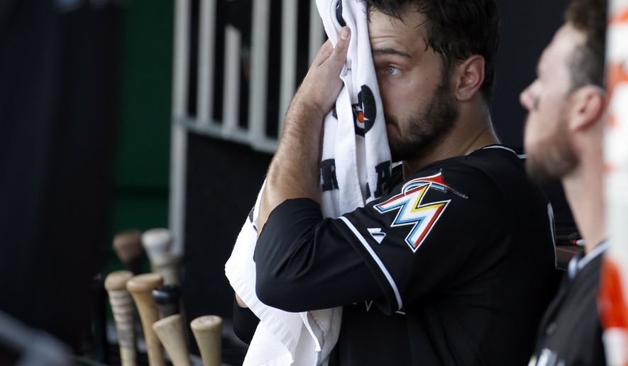 Miami Marlins starting pitcher Jarred Cosart wipes his face in the dugout during the third inning of the first baseball game of a doubleheader against the Washington Nationals at Nationals Park, Friday, Sept. 26, 2014, in Washington. (AP Photo/Alex Brandon)