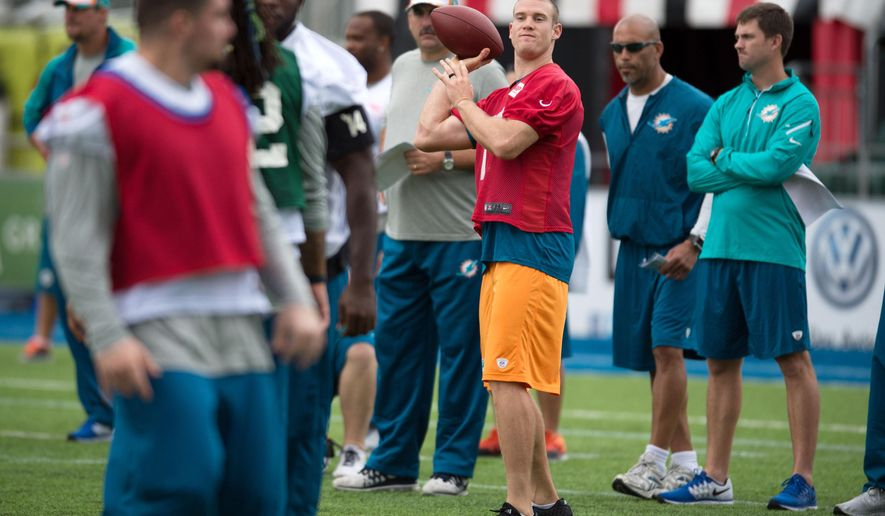 Miami Dolphins quarterback Ryan Tannehill, centre, prepares to throw a pass during a training session at Allianz Park, London, England, Friday, Sept. 26, 2014. The Miami Dolphins will play the Raiders in an NFL football game at London's Wembley Stadium on Sunday Sept. 28. (AP Photo/Tim Ireland)